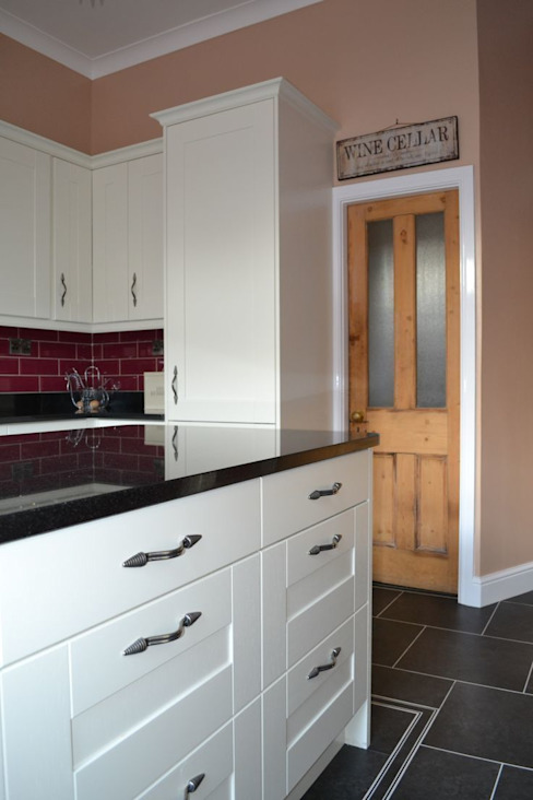 Wentworth Kitchen Units in Alabaster with black granite worktops and cranberry wall tiles. de Statement Kitchens Moderno