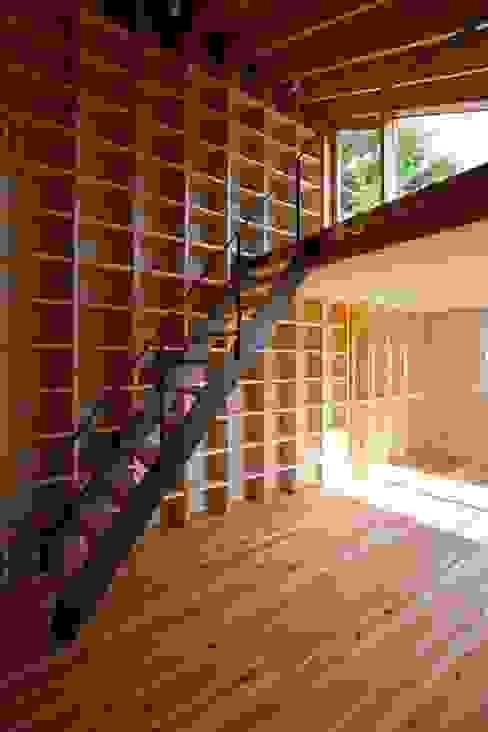 リビングの壁面一杯に本棚を造りました。階段を上ると屋上です! 根岸達己建築室 クラシックデザインの リビング 無垢材 ベージュ