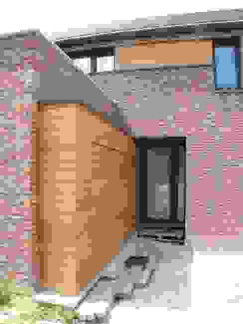 Le bardage qui dissimule une porte de garage guide vers la porte d'entrée principale. Maisons modernes par dune Architecture sprl Moderne