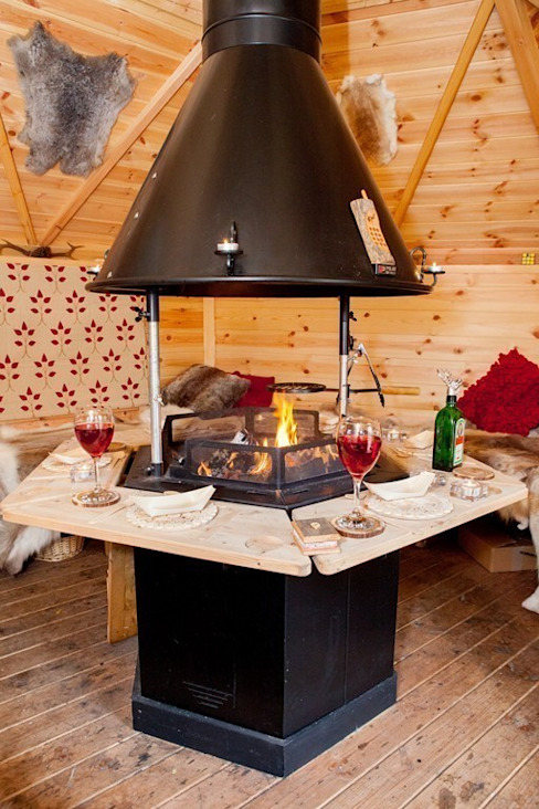 The interior of a 10m² barbecue cabin with the fire going on a Sunday afternoon. من Arctic Cabins إسكندينافي
