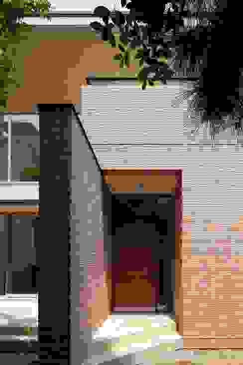 壁に誘われてアプローチする玄関: シーズ・アーキスタディオ建築設計室が手掛けた家です。,
