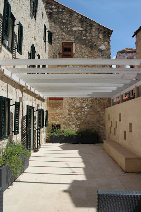 pergola and external wall in the courtyard od drawing agency ltd Minimalistyczny