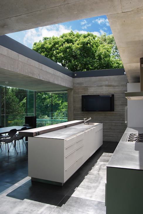 Kitchen with sliding rooflight to create open-air court by Eldridge London Minimalist