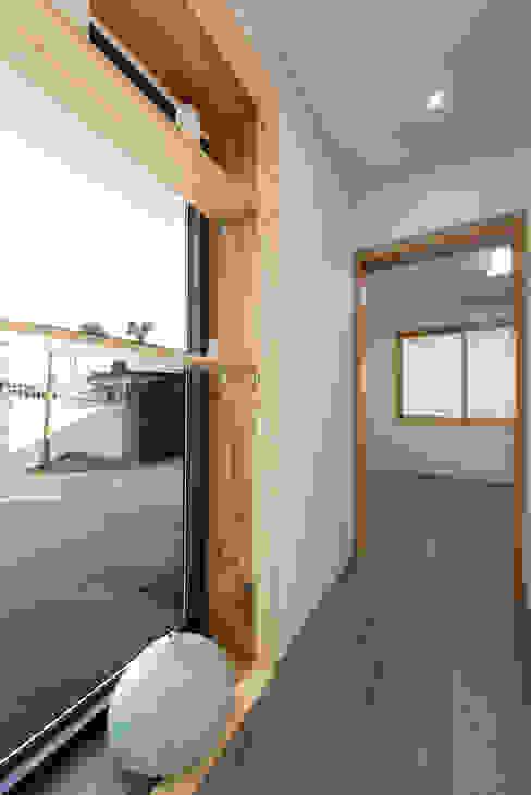 안방과 거실을 이어주는 복도, 창밖으로 보이는 마당: 비에스디자인건축사사무소의  복도 & 현관