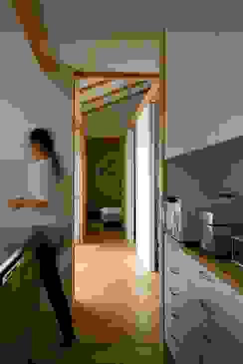 袋井の家 キッチンから廊下を見る。: 木名瀬佳世建築研究室が手掛けたキッチンです。,モダン 木 木目調