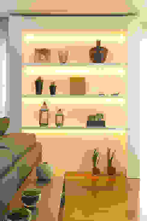 Estante em marcenaria, com pintura branca alto brilho e iluminação em led por Liliana Zenaro Interiores Moderno