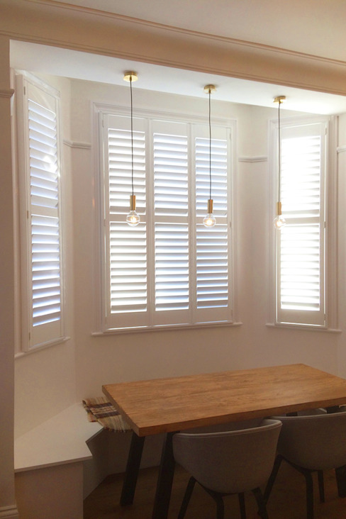 Dining room shutters for bay windows:  Living room by Plantation Shutters Ltd,
