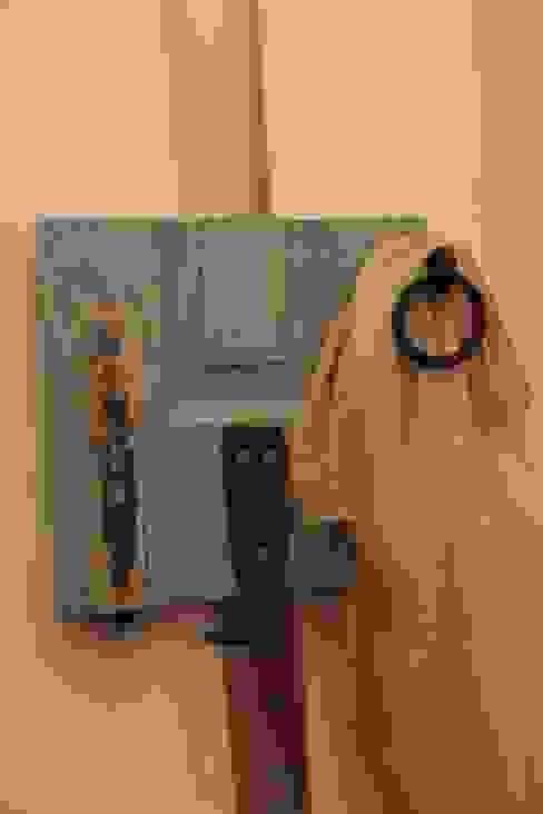 Cabide de uma parte de uma portada com ferragens.: Corredor, hall e escadas  por Pó de Giz,