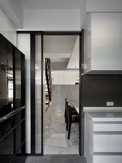 Movable slide doors reduces precious space between dining room and kitchen. Modern style kitchen by 大集國際室內裝修設計工程有限公司 Modern