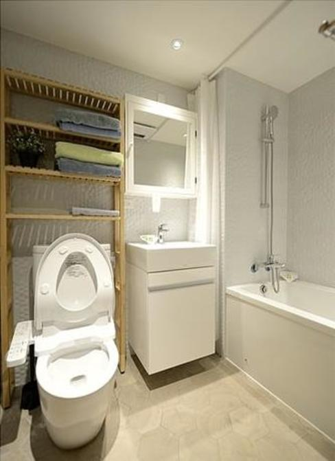 以『仿圓形馬賽克效果壁磚』與『復古溫暖木紋六角蜂巢地磚』,圍塑出北歐風格效果的衛浴空間。 現代浴室設計點子、靈感&圖片 根據 大觀創境空間設計事務所 現代風