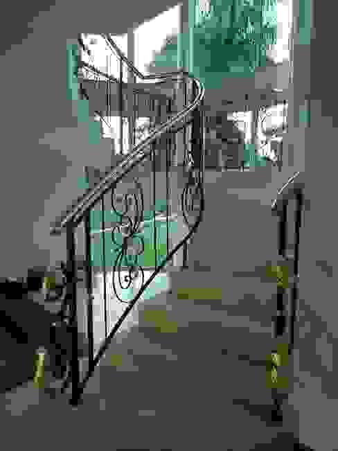 Escada com guarda-corpo em ferro e latão por Penha Alba Arquitetura e Interiores Clássico Ferro/Aço