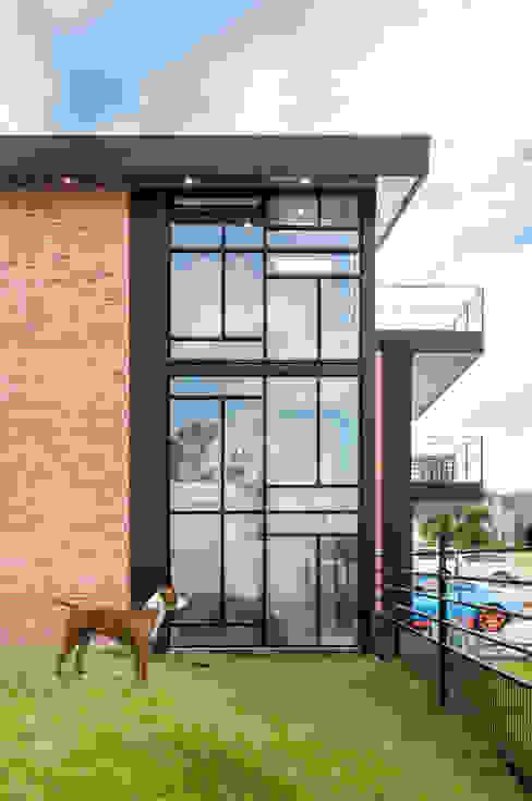 fachada lateral: Casas unifamiliares de estilo  por aaestudio