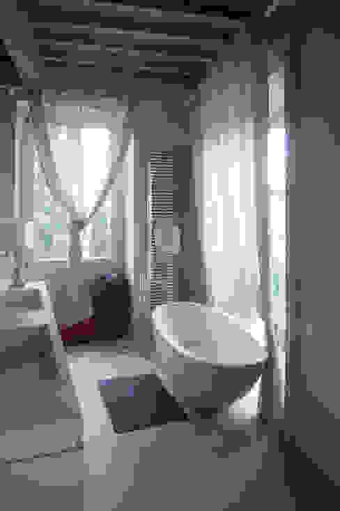 Bagno con rivestimenti, lavabo e vasca in travertino Bagno in stile classico di Pietre di Rapolano Classico Pietra