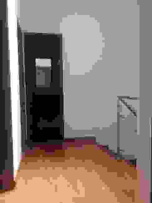 Pasillo con piso de laminado de madera, escalera y vista a cuartos: Pasillos y vestíbulos de estilo  por Erick Becerra Arquitecto,