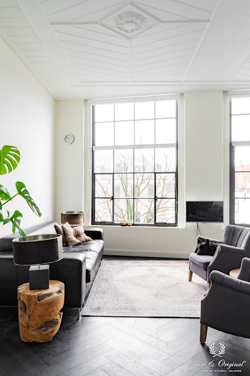 Lichte woonkamer met witte wanden en zwarte stalen kozijnen:  Woonkamer door Pure & Original, Modern