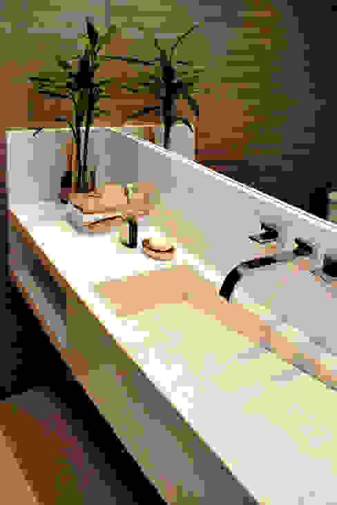 Lavabo com cuba esculpida e revestimento listrado Banheiros minimalistas por RAWI Arquitetura + Design Minimalista Pedra