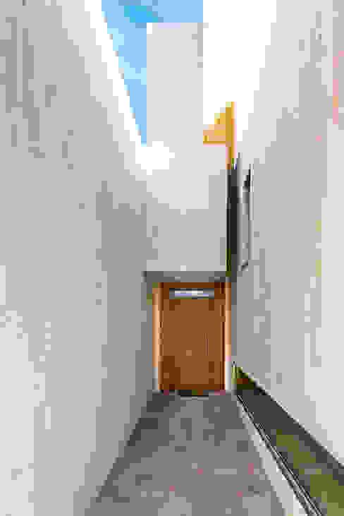 Puerta de entrada a la casa protegida de la meteorología. OOIIO Arquitectura Puertas de entrada Madera Marrón