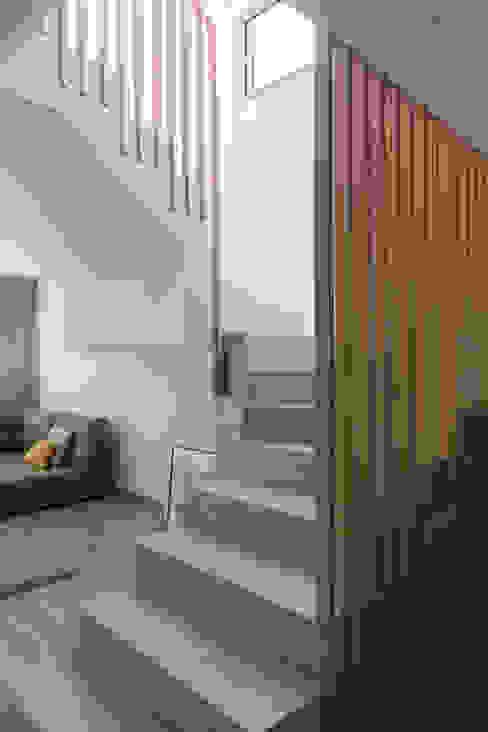 Escalera de microcemento con barandilla de madera maciza, diseñado a medida por nuestro estudio. HoffmannWehr | Arquitectura & diseño interior Escaleras Madera Gris