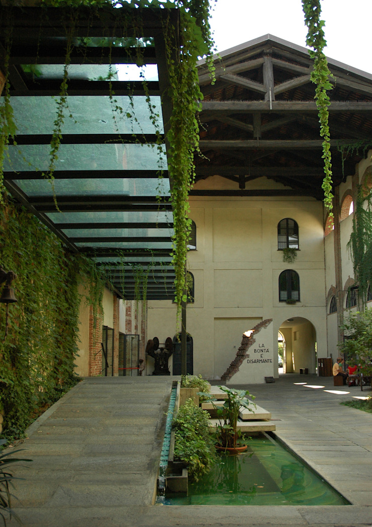 Entrance to SER.MI.G Chapel Country style gardens by Comoglio Architetti Country