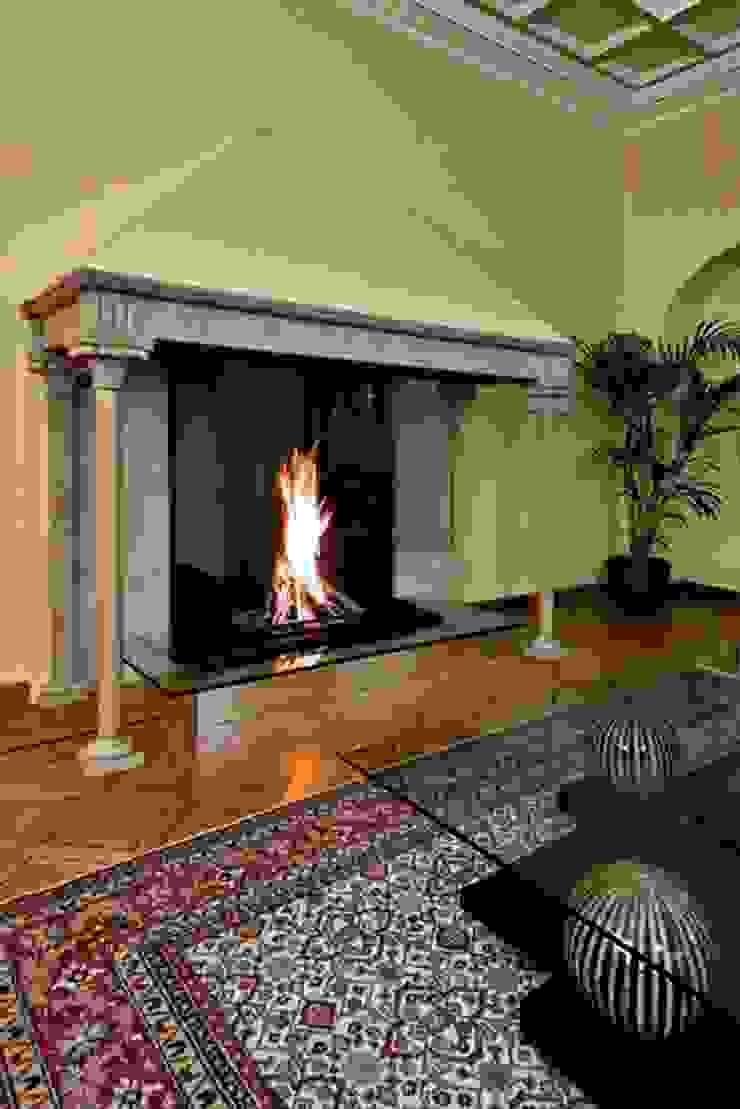 Modern glass fireplace inside an original Italian style fireplace por Bloch Design Clássico