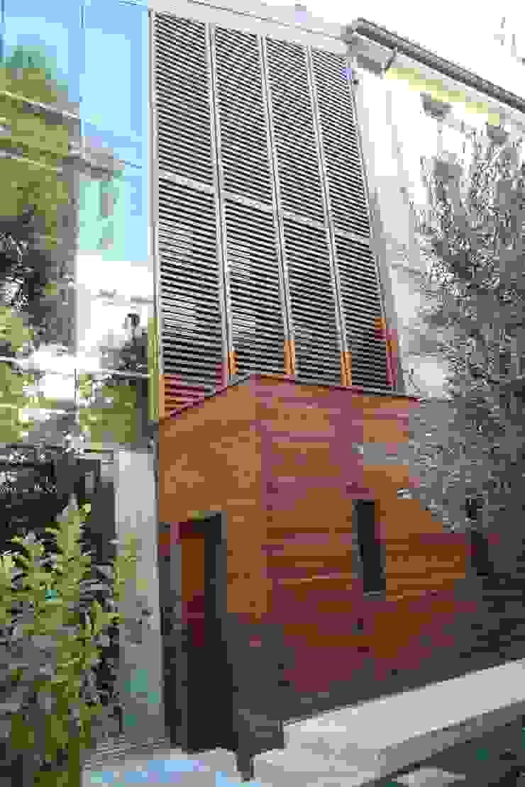 Dettaglio della facciata ventilata in vetro con frangisole in legno. Cumo Mori Roversi Architetti Case moderne