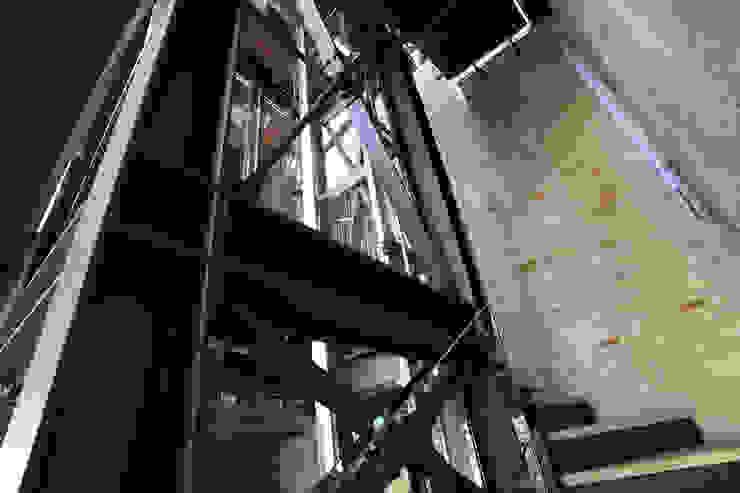 Dettaglio della struttura in ferro che contiene l'ascensore, attorno alla quale si sviluppa la scala. Cumo Mori Roversi Architetti Ingresso, Corridoio & Scale in stile moderno