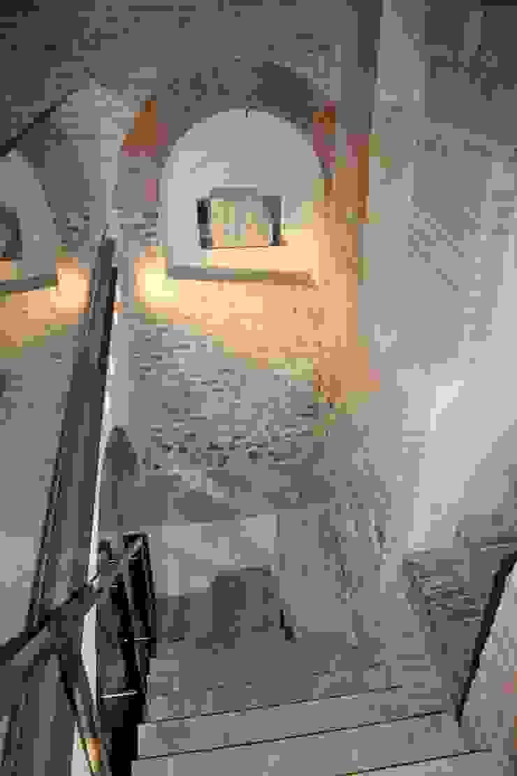 La scala che conduce al piano interrato della torre: in evidenza alcuni resti archeologici rinvenuti durante gli scavi. Cumo Mori Roversi Architetti Ingresso, Corridoio & Scale in stile moderno