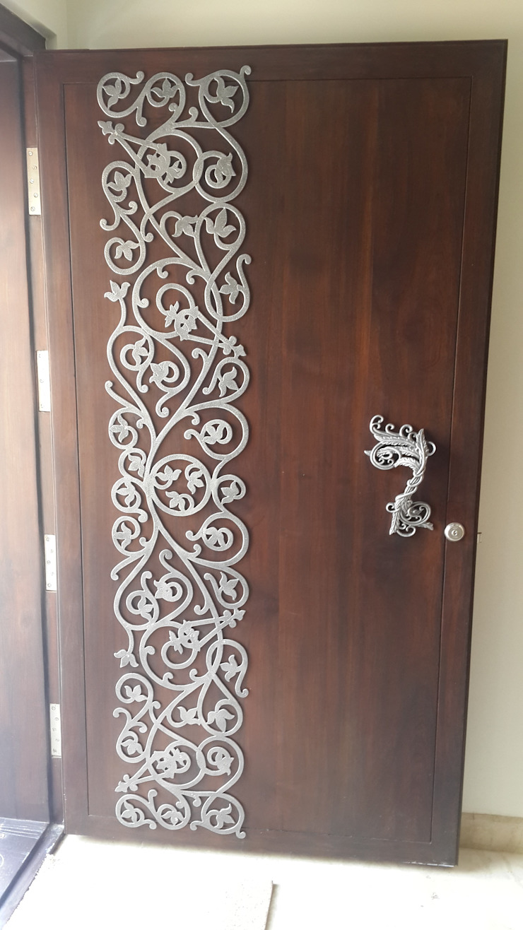 white metal applique on the main door : modern  by Hasta architects,Modern