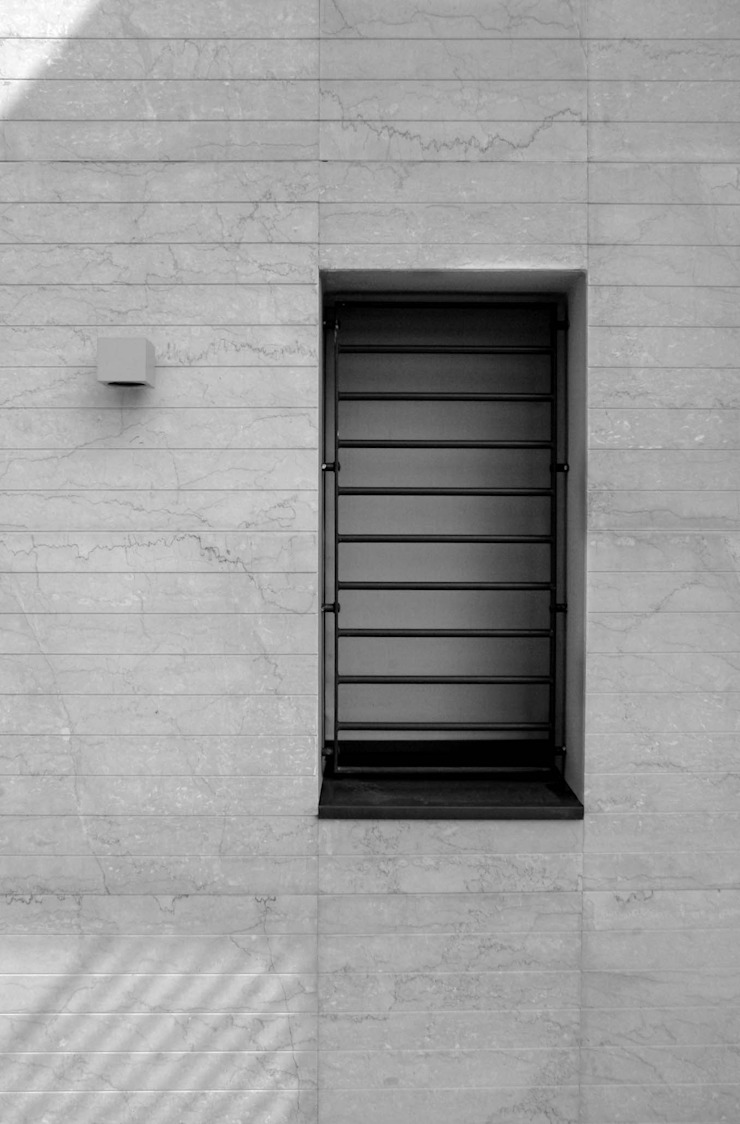 Rivestimento esterno realizzato in pietra locale Finestre & Porte in stile moderno di boschi + serboli architetti associati Moderno