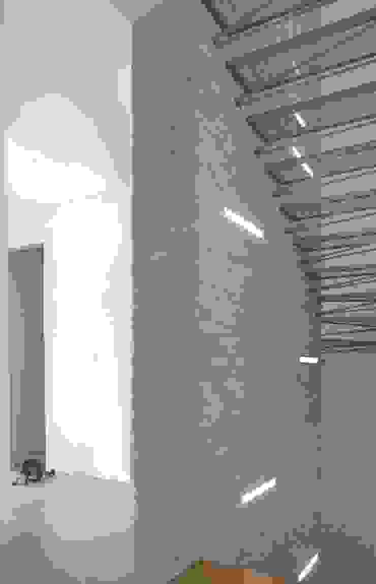Setto portante centrale rivestito in pietra e completato da corpi illuminanti Ingresso, Corridoio & Scale in stile moderno di boschi + serboli architetti associati Moderno