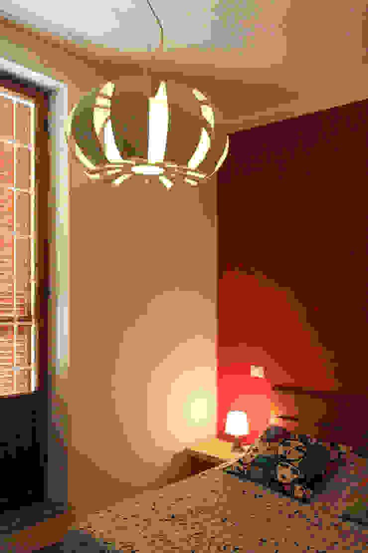 dettaglio del lampadario e della parete rossa nella camera da letto matrimoniale Camera da letto moderna di EMC2Architetti Moderno