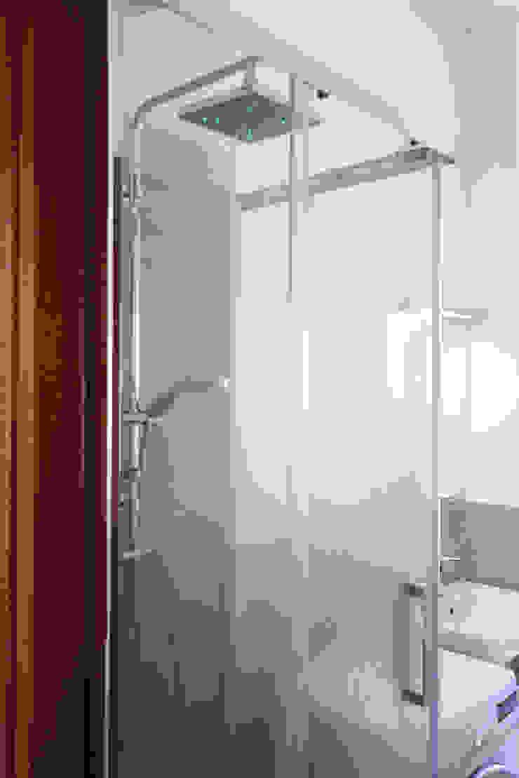 Dettaglio del box doccia in cristallo con soffione dotato di cromoterapia Bagno moderno di EMC2Architetti Moderno