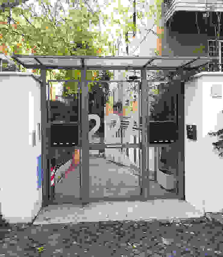 Dettaglio del portone d'ingresso Case moderne di MOMARCH Moderno