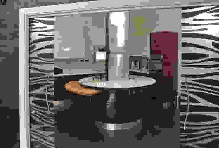 la cucina vista dalla zona giorno attraverso la porta scorrevole in vetro di GIOIA Biagio ARCHITETTO Moderno