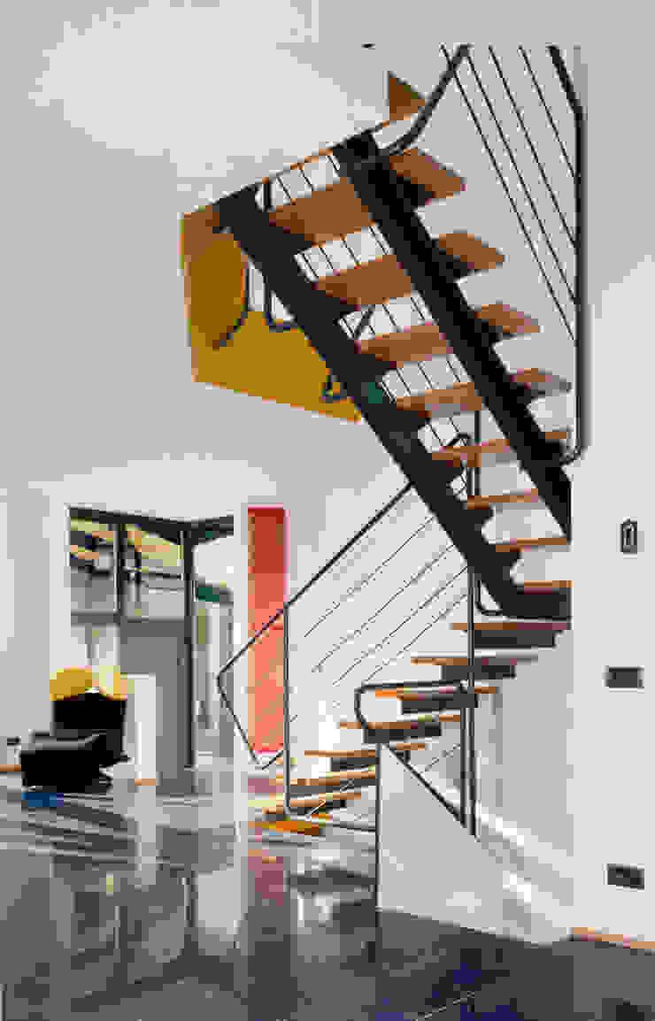 l'ingresso e la scala che personalizza e divide la zona giorno e la cucina Ingresso, Corridoio & Scale in stile moderno di RoccAtelier Associati Moderno