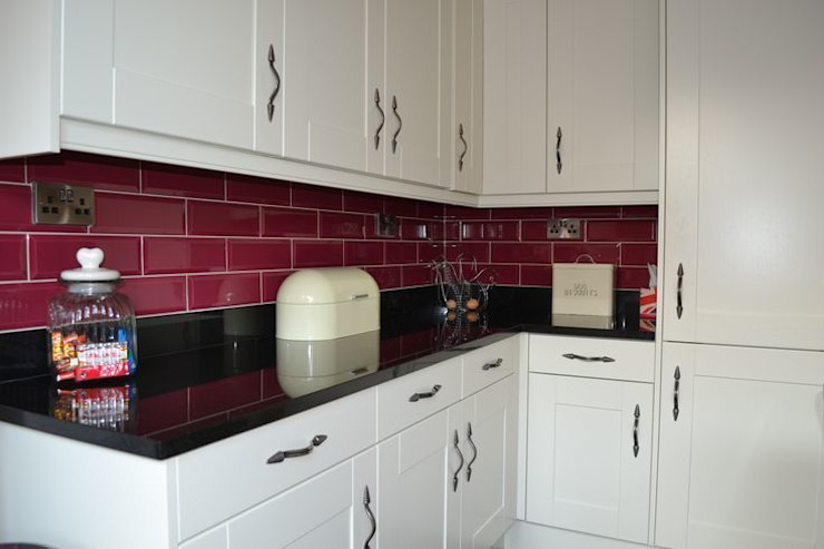 Wentworth Kitchen Units in Alabaster with black granite worktops and cranberry wall tiles. par Statement Kitchens Moderne