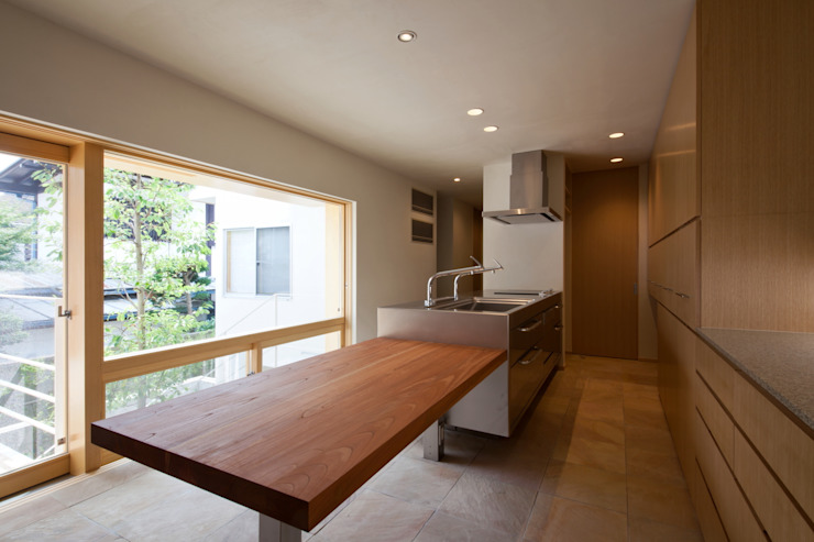中庭の緑を見ながら家事ができるキッチン モダンな キッチン の 根岸達己建築室 モダン 無垢材 多色