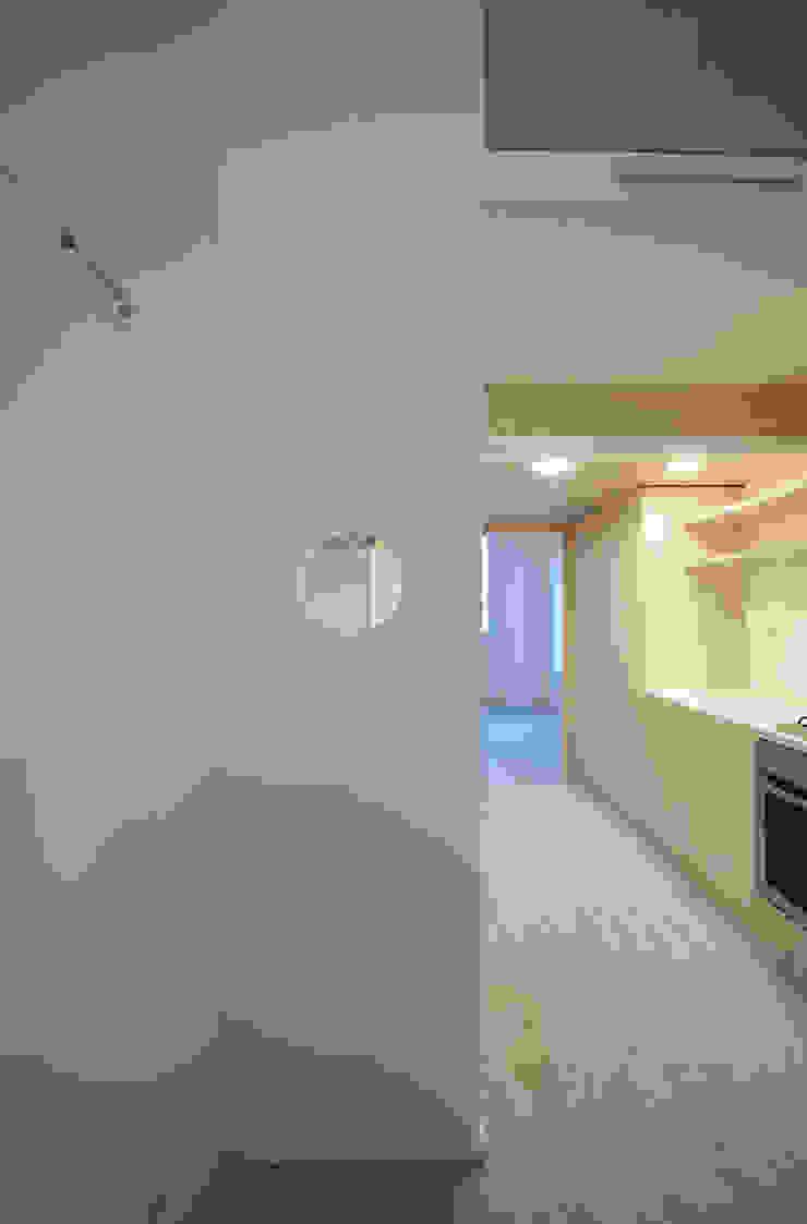 vista dal soggiorno verso la cucina attraverso l'oblò Cucina minimalista di supercake Minimalista