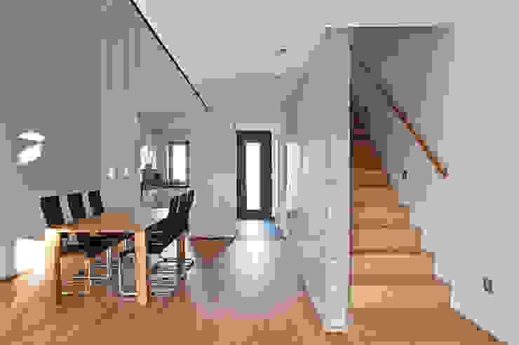 Helles Wohnzimmer mit Essbereich, Luftraum und Treppe Moderne Wohnzimmer von Lecke Architekten Modern