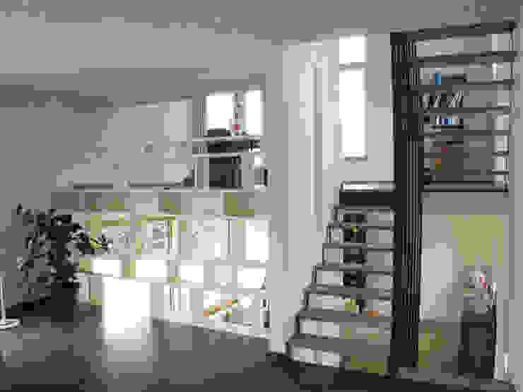 Escalier à claire-voie et bibliothèque délimitent en offrant des contacts visuels. par dune Architecture sprl Minimaliste