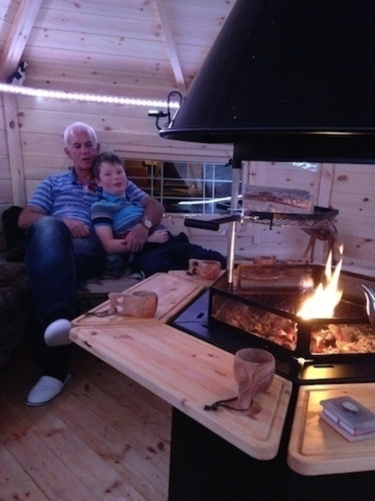 Snuggling up with Grandad by the fire. Jardin scandinave par Arctic Cabins Scandinave