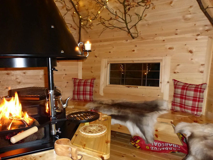 The interior of a 10m² cabin, fire going lovely cushions and reindeer skins on the benches. Scandinavian style garden by Arctic Cabins Scandinavian