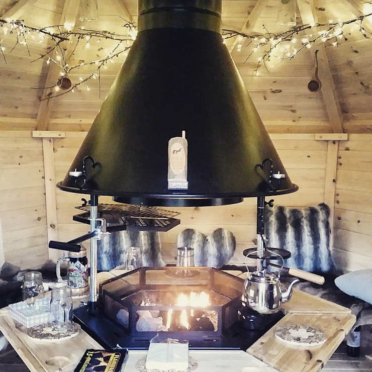 Looks so comfy - gorgeous lights, cushions and a real fire. Scandinavian style garden by Arctic Cabins Scandinavian