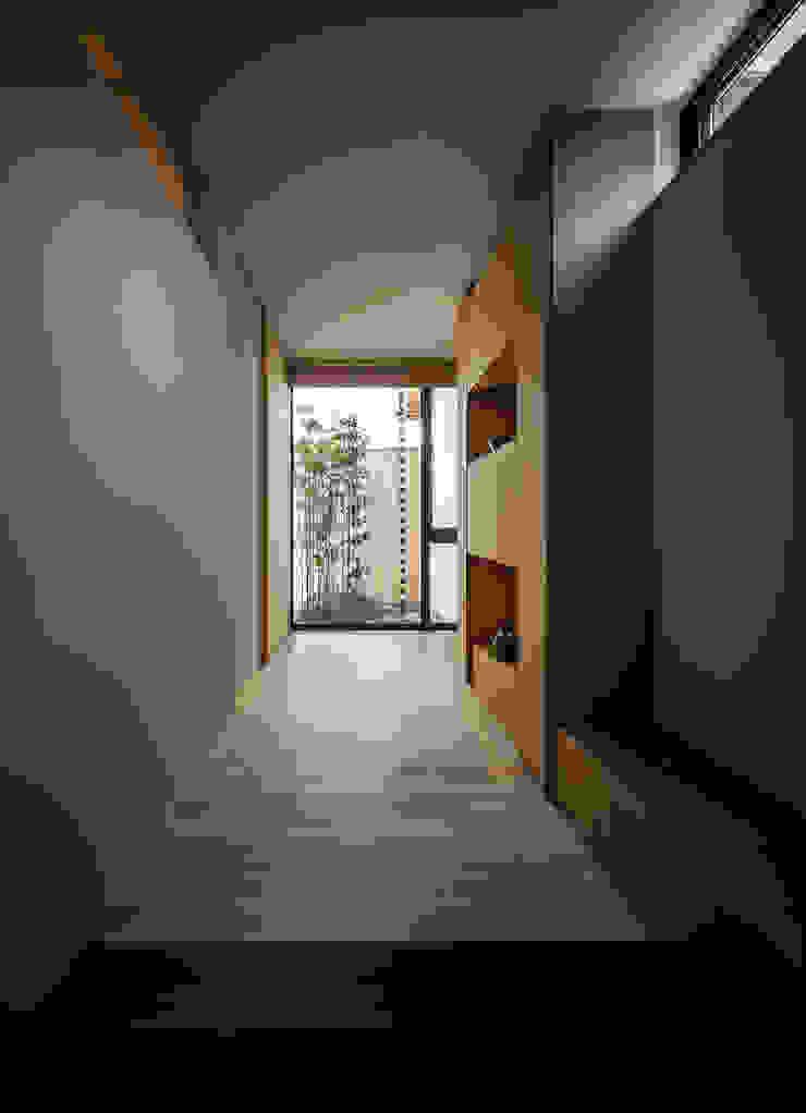 それぞれの庭の家 玄関から[黒竹と苔むす岩の庭]をのぞむ 和風の 玄関&廊下&階段 の 株式会社seki.design 和風