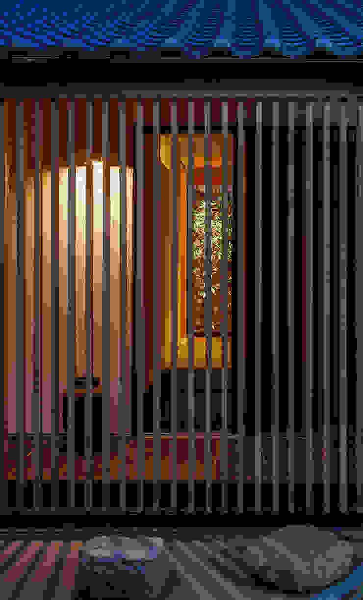 それぞれの庭の家 縦格子越しに玄関、[黒竹と苔むす岩]を見通す 日本家屋・アジアの家 の 株式会社seki.design 和風