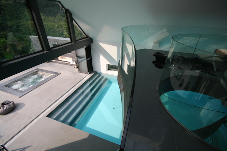 Indoor pool with waterfall features, sauna and stainless steel spa by Tanby Swimming Pools Modern