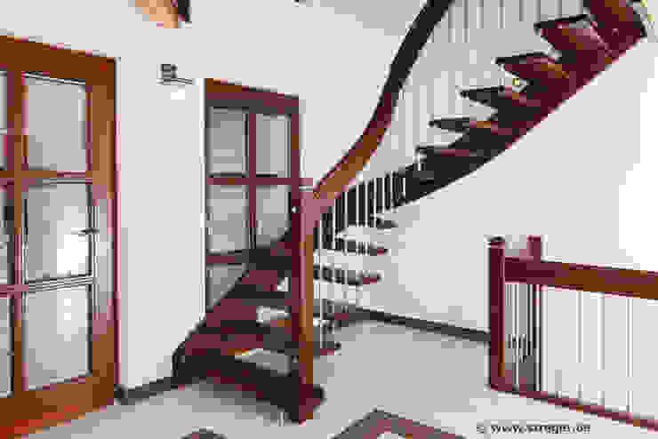 Die Tragbolzentreppe aus dem heimischen Holz der Buche wurde auf Mahagoni gebeizt STREGER Massivholztreppen GmbH Moderner Flur, Diele & Treppenhaus