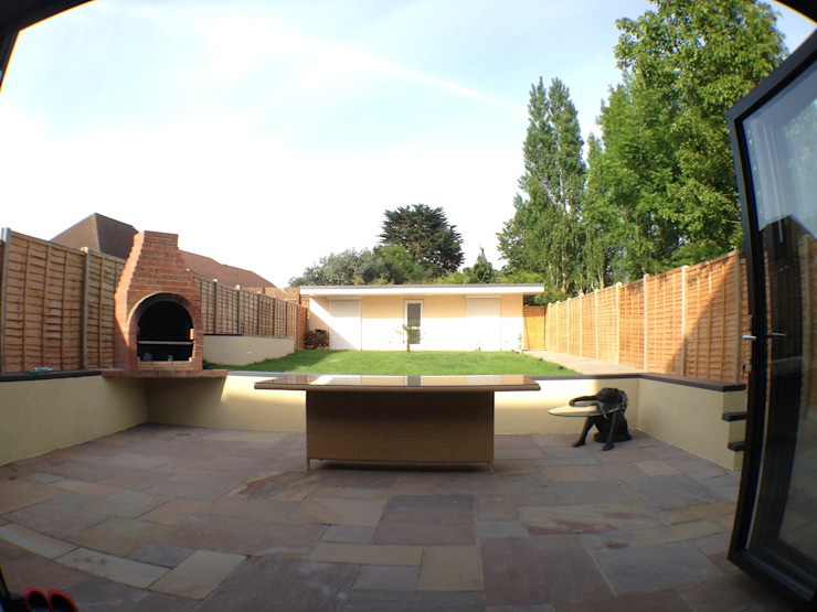 patio with raised sitting area and suspended brick barbecue Jardins modernos por Progressive Design London Moderno