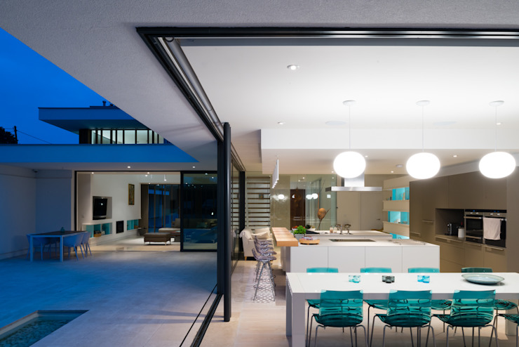 River House - Internal/external night view of dining room and kitchen Selencky///Parsons Salas de jantar modernas