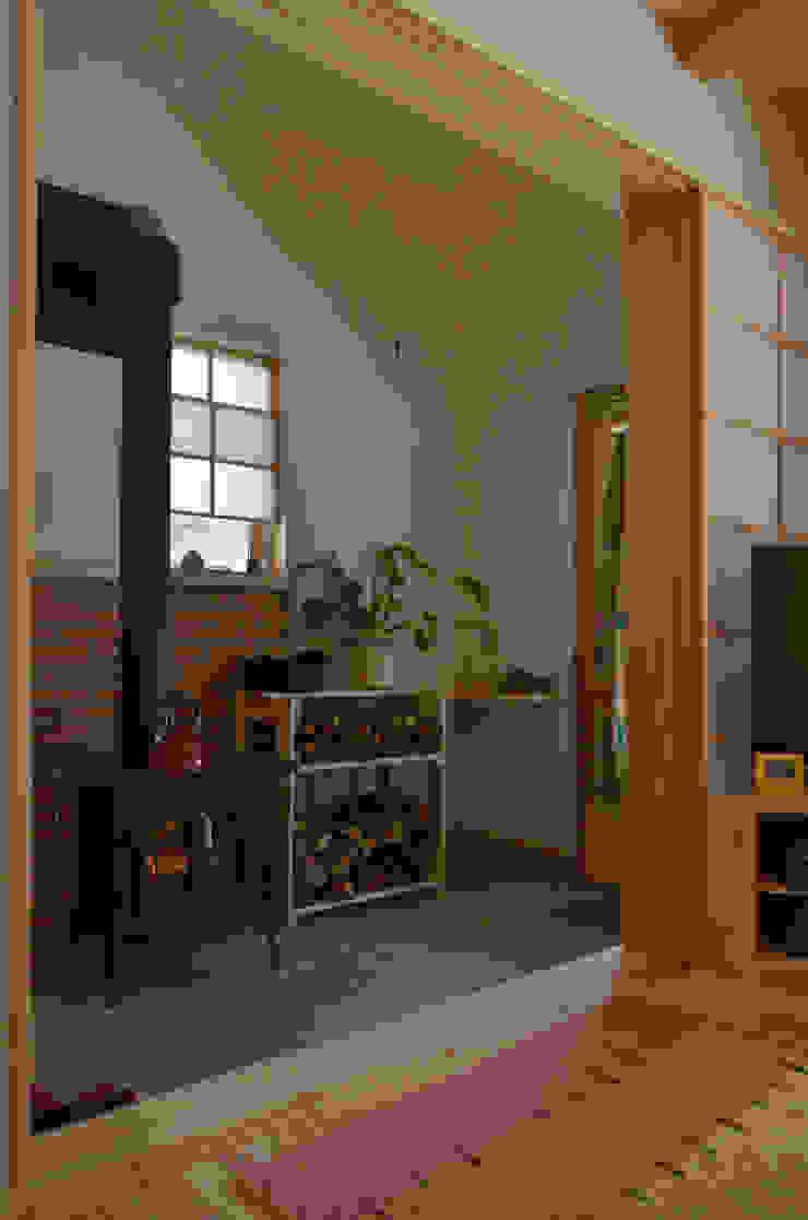 玄関土間にストーブ: (株)誠設計事務所が手掛けたアジア人です。,和風